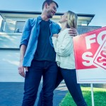 Couple standing in front of a new home. They are standing next to a for sale sign with a sold sticker. They are buying or selling this real estate. They are both wearing casual clothes and embracing. They are smiling and he has a beard. The house is new and contemporary with a brick facade. Copy space